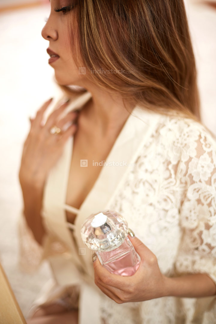 a young beautiful Asian woman in a beige lace dressing gown put on morning makeup and scented with perfume . shallow depth of focus. selective focus
