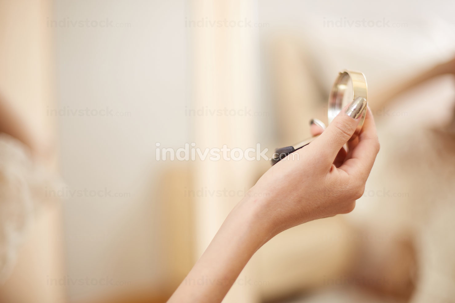 a young beautiful Asian woman in a beige lace dressing gown put on morning makeup and uses eye shadow, blush and Foundation . in the bedroom . shallow depth of focus. selective focus
