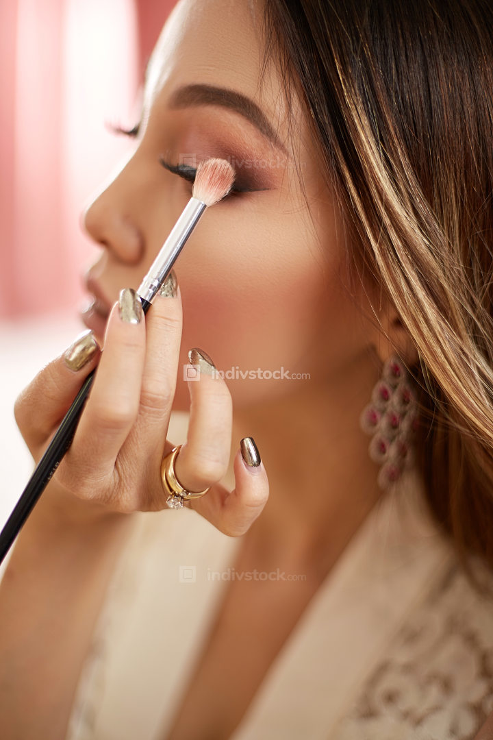 a young beautiful Asian woman in a beige lace robe put on morning makeup and uses eye shadow, blush and Foundation . in the bedroom . shallow depth of focus. selective focus