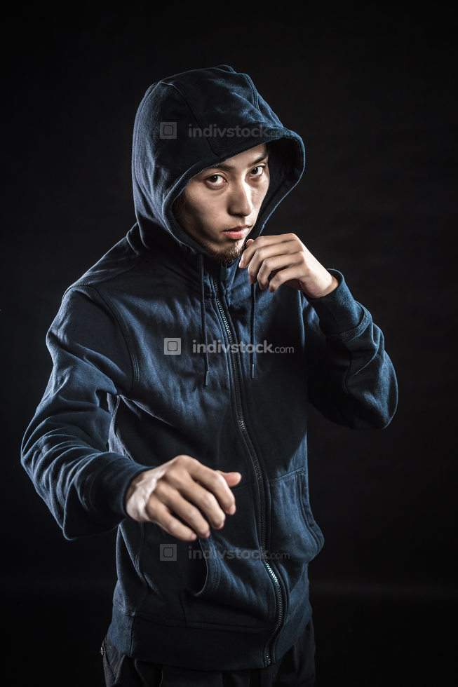 Aggressive fighter in hood while punching against black backgrou