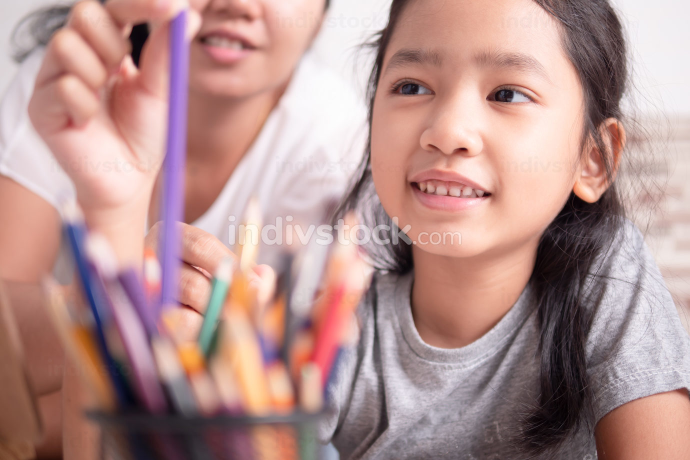 Asian little girl and a woman selecting a color for painting