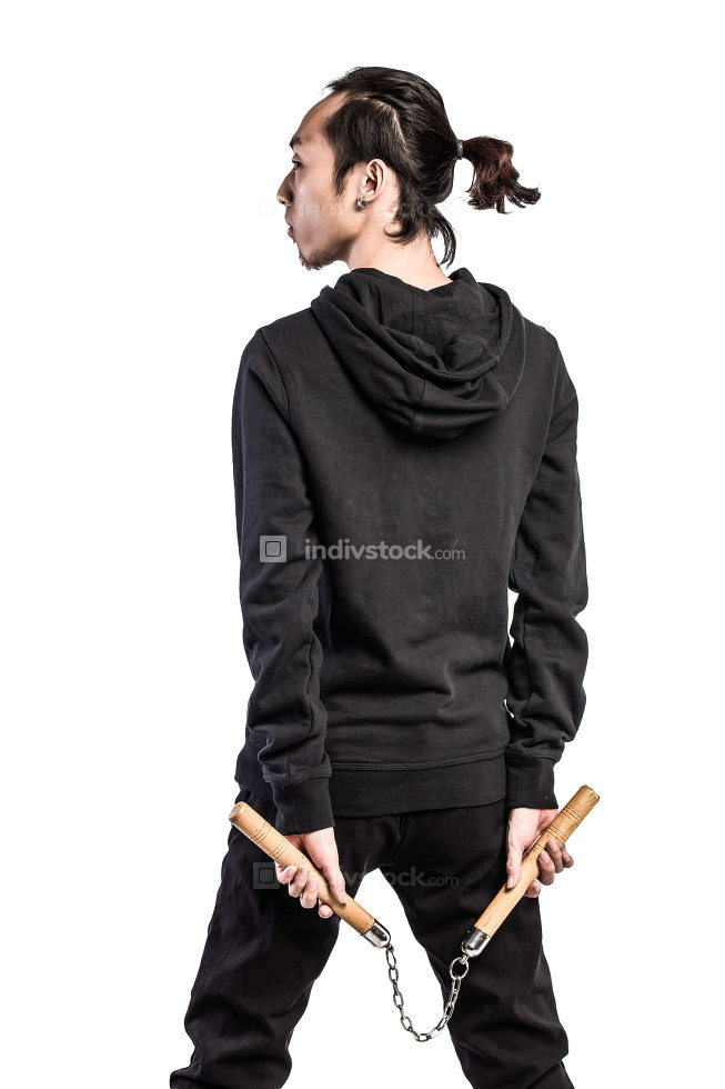 asian man in a hood is using nunchaku