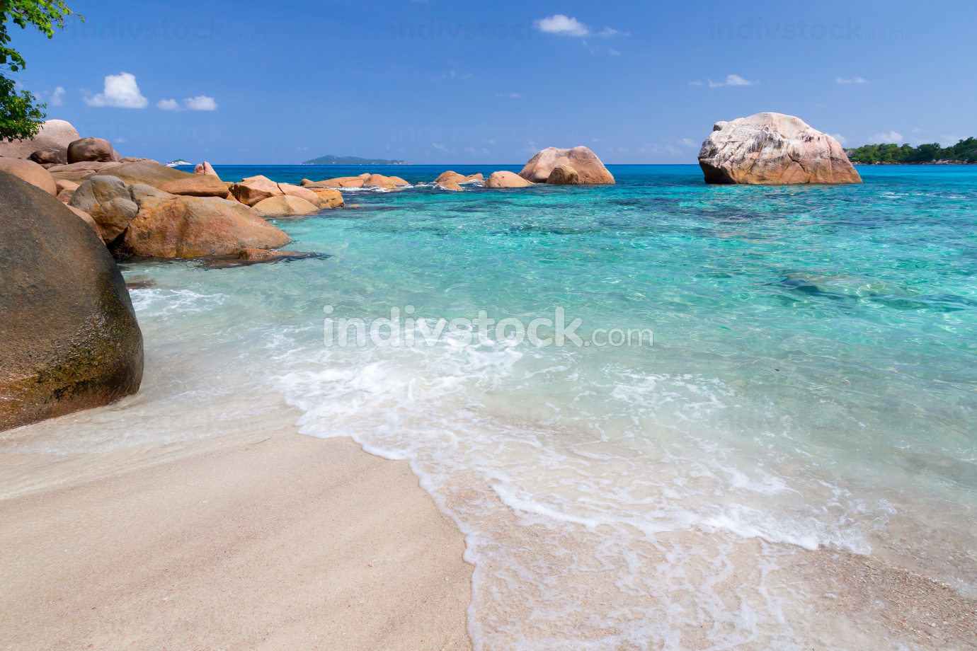 Beach with blue water and blue sky and white sand and some rocks