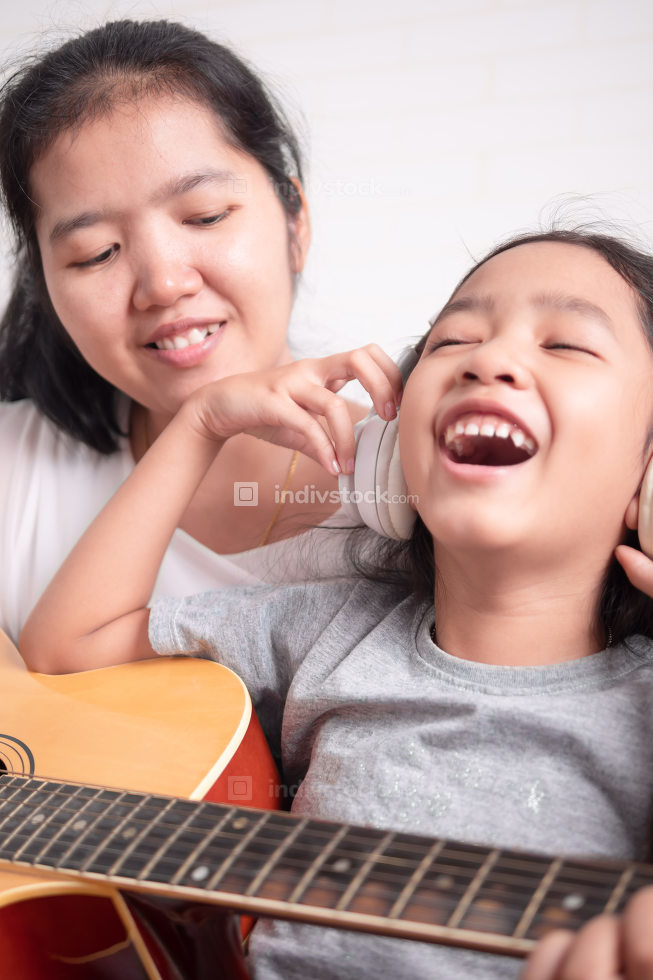 Children take a headphone and laugh with happiness