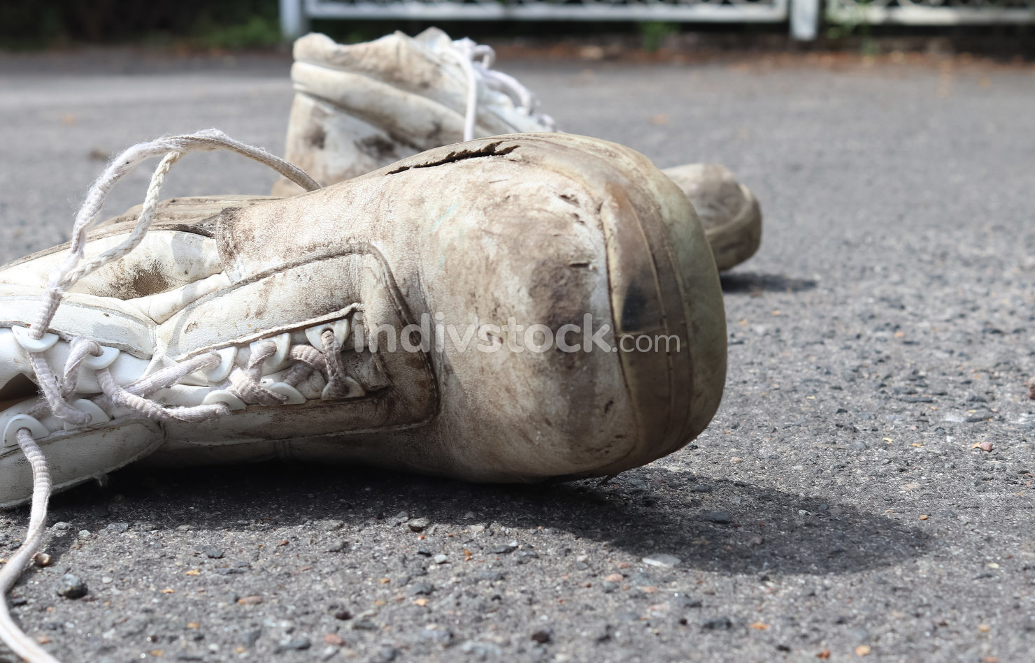 Concept of old shoes left on an ashpalt road with copy space for
