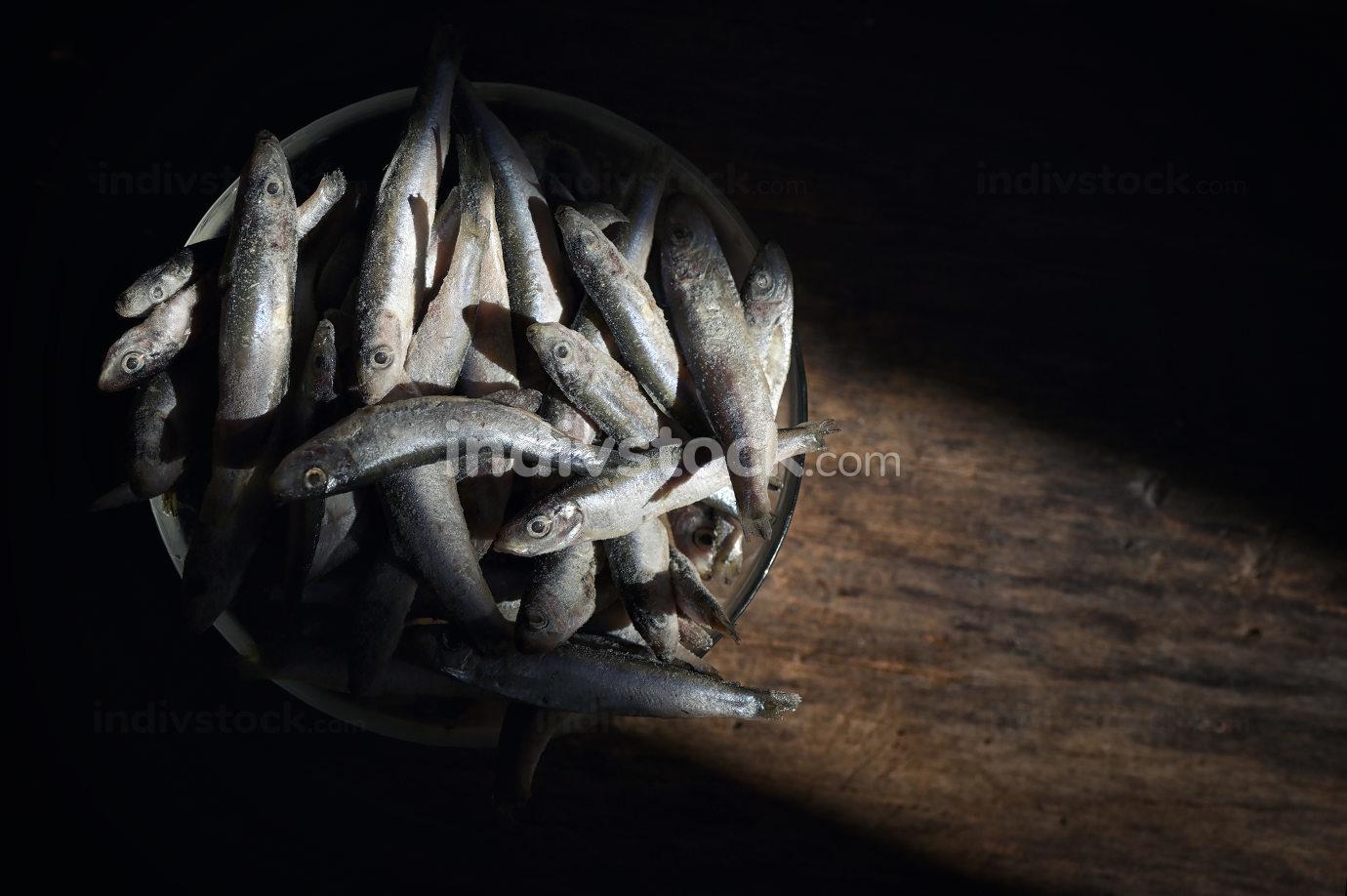 Frozen sprat fish on wooden table