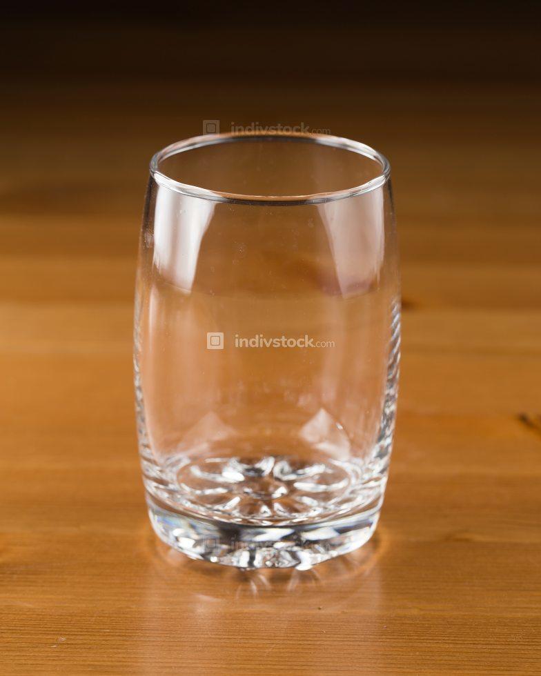 Glass empty on wooden floor.