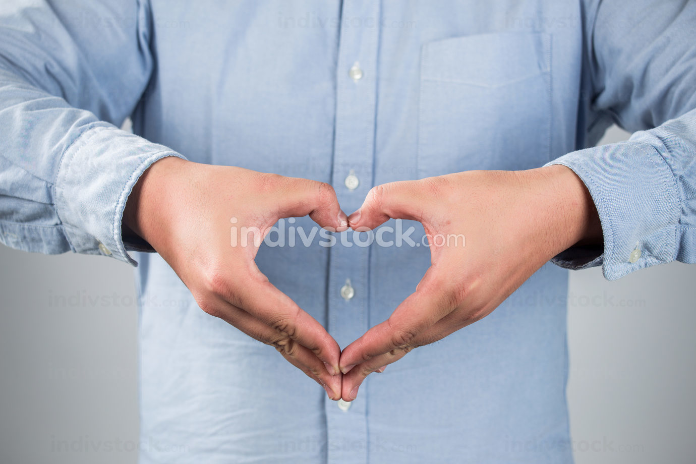 Closeup portrait handsome smiling young business man makes the heart using fingers, hands, isolated grey wall background. Positive human emotions, facial expressions, feelings, body language, attitude