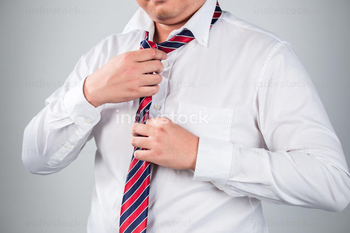 Businessman in blue suit tying the necktie  good