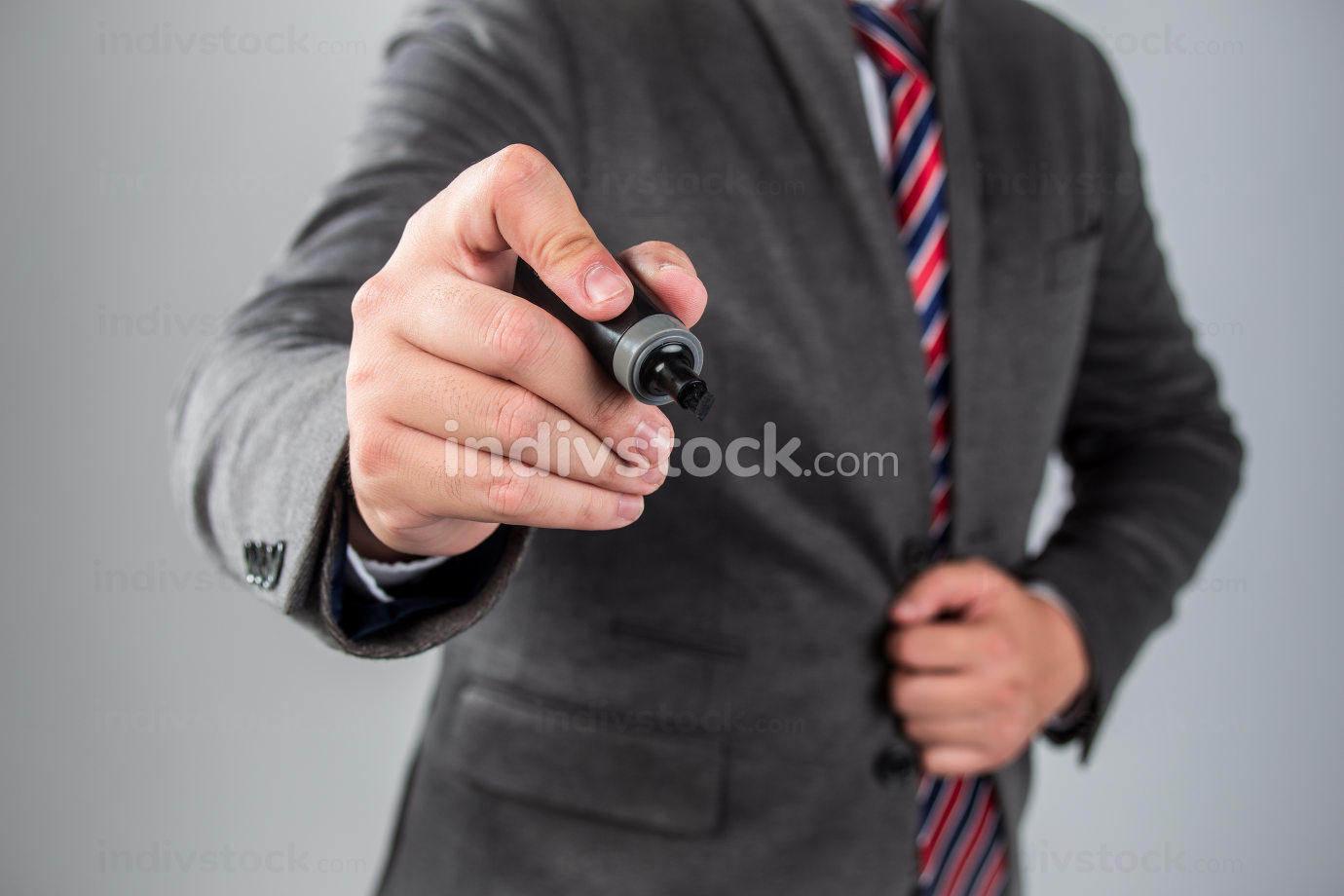 Businessman standing posture hand hold a pen isolated on over grey background
