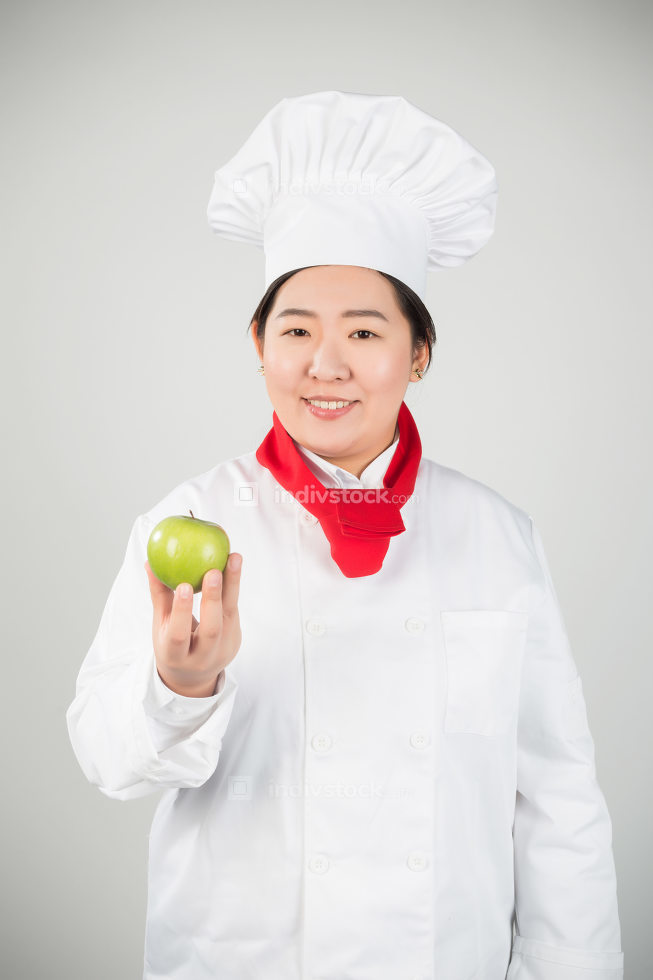 cooking and food concept - smiling female chef, holding a green apple