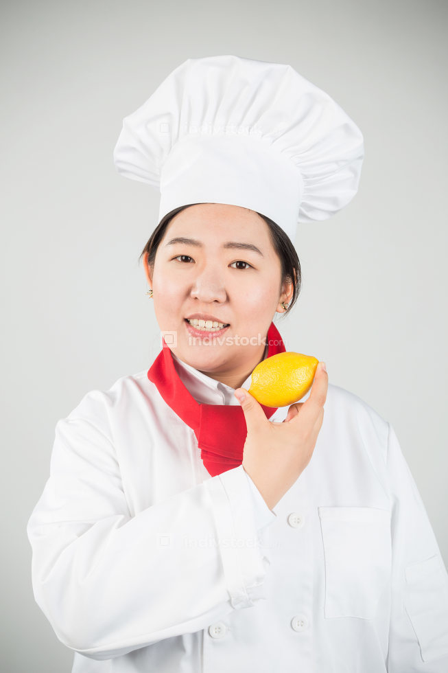 cooking and food concept - smiling female chef, holding a lemon