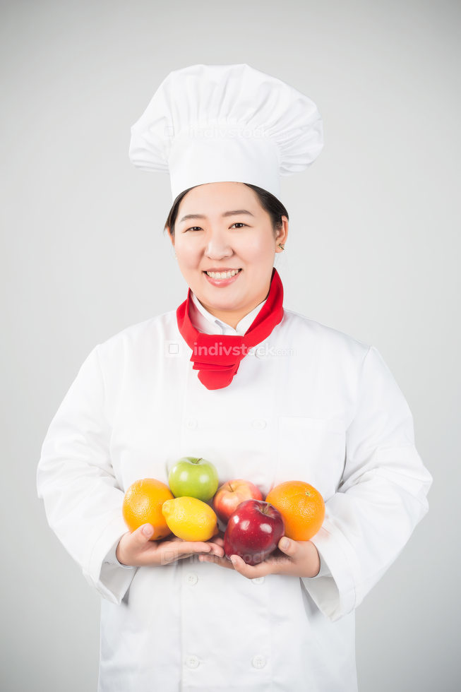 girl in chef's hat with fruits on a white background