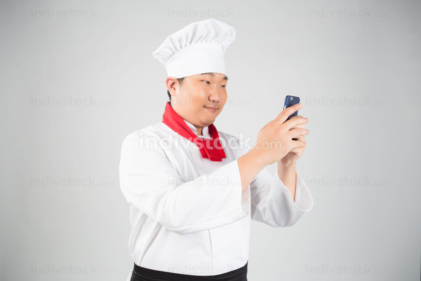 Young Cook With Red Scarf Looking At Phone Surprised, Isolated