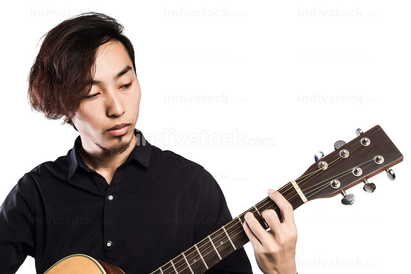 Young man playing guitar on white background looking to the camera