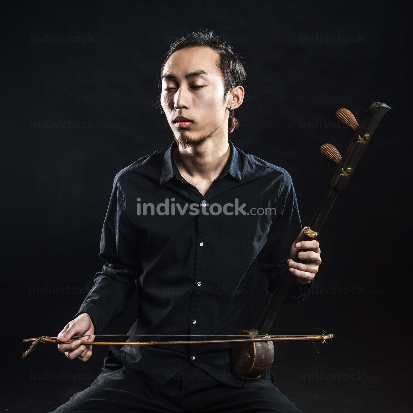 man is playing huqin isolated on black