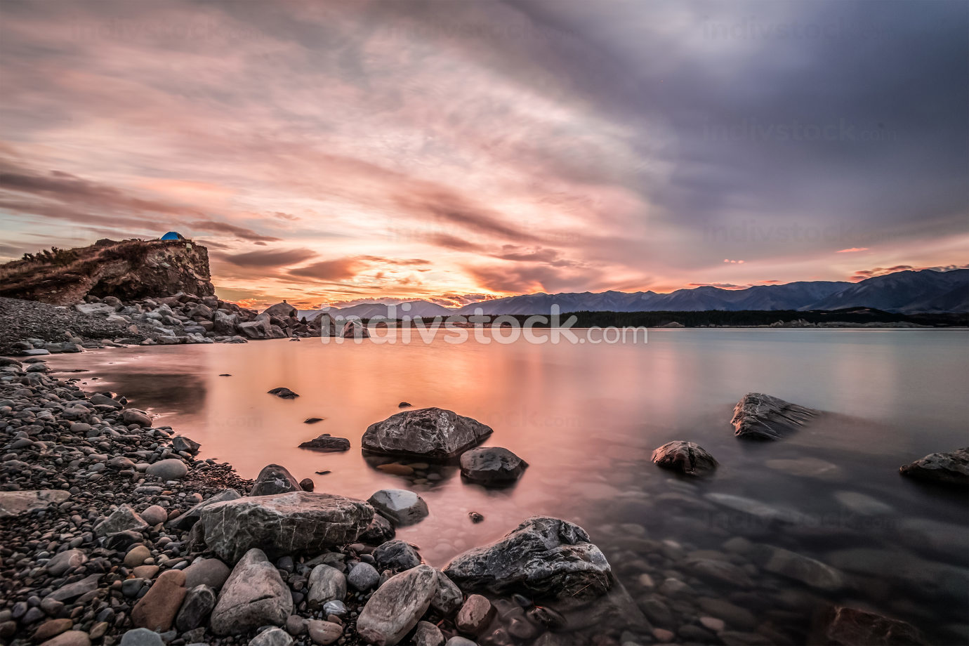 Sunset at Mount Cook National Park alongside Lake Pukaki with snow capped Southern Alps basking in the late winter afternoon's golden light. The setting sun cast vivid pastel  hues on the sky.