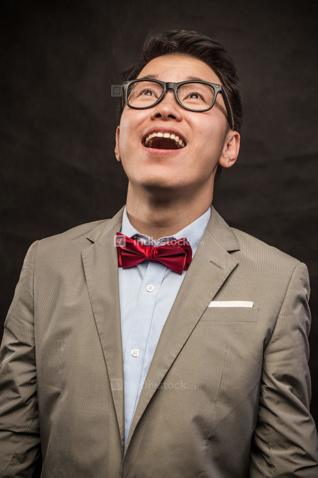 Young man wearing glasses smiling. Isolated on grey background.