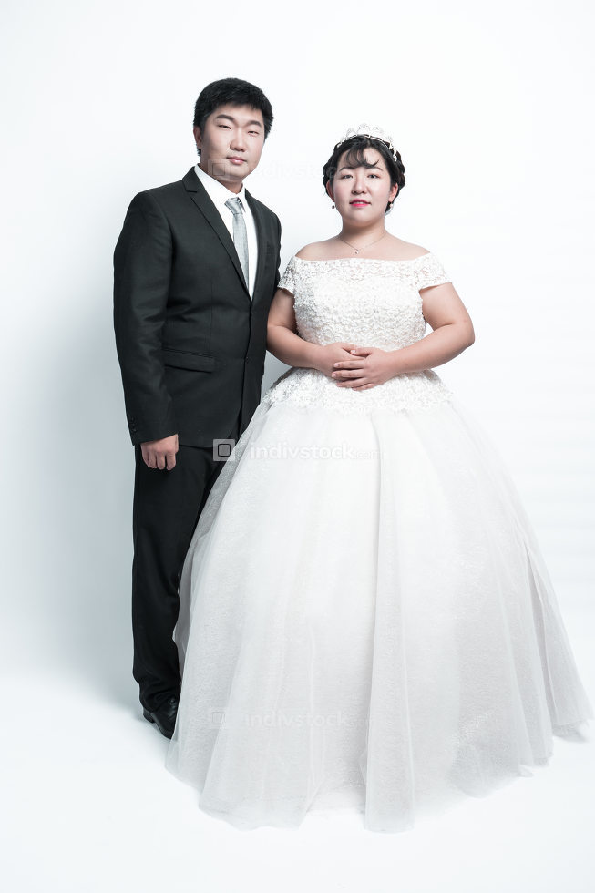 Full length portrait of a young groom carrying a bride in his hands isolated on white background