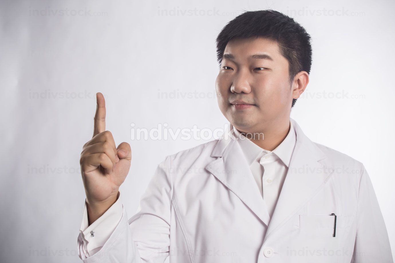 healthcare, profession, people and medicine concept - happy smiling male doctor in white coat pointing finger up