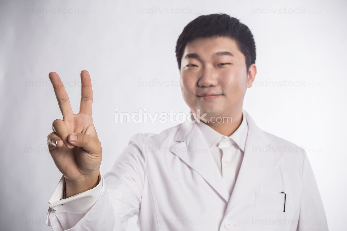 mature doctor making the victory sign while holding a notepad on white background