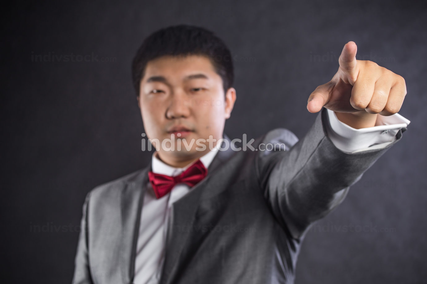 Business man pointing the finger at you, isolated on black background