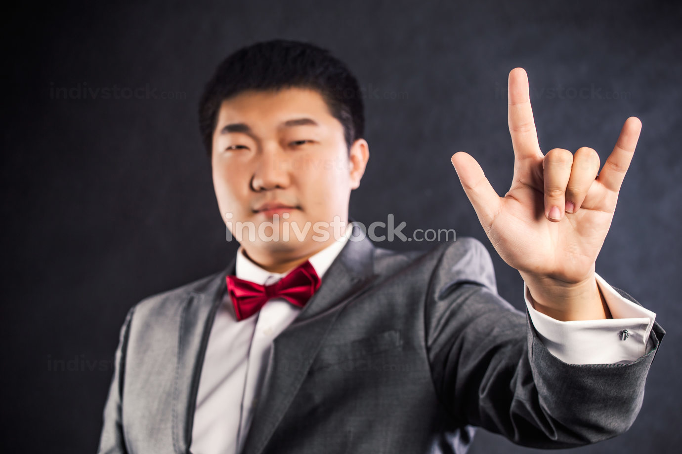 man with his hand showing love sign black background