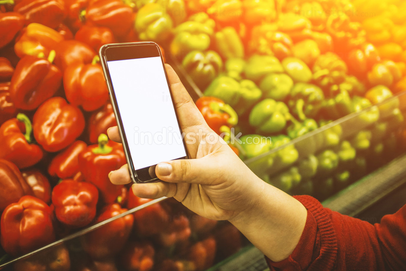 Hand holding smart phone on blurred market background - shopping online nice mockup