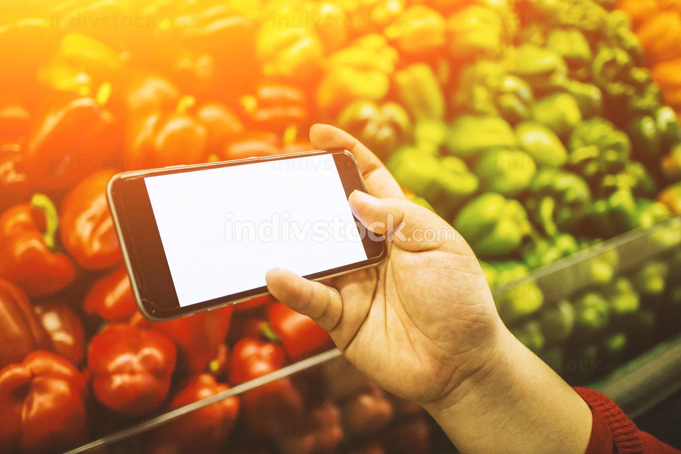 Hand holding smart phone on blurred market background - shopping online nice mockup