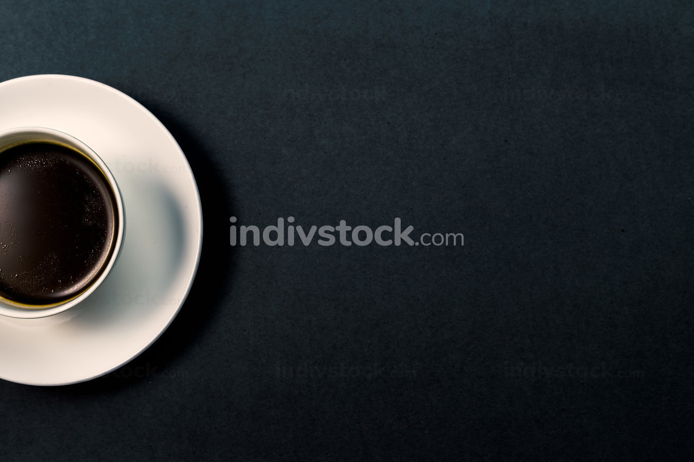 A cup of coffee with heart pattern in a white cup on grey background