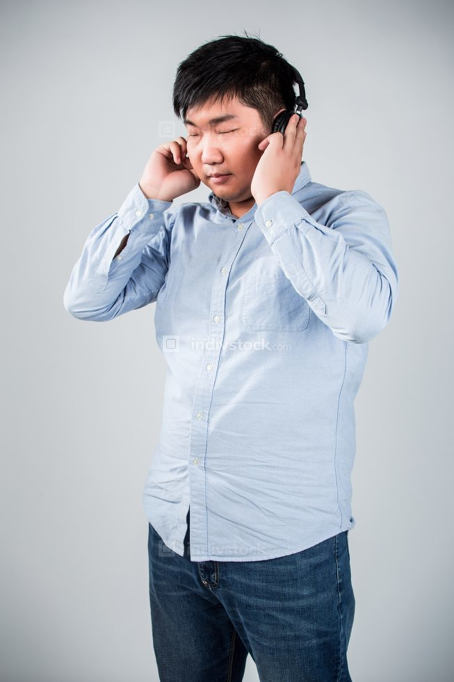 man in headphones holding mobile phone and smiling