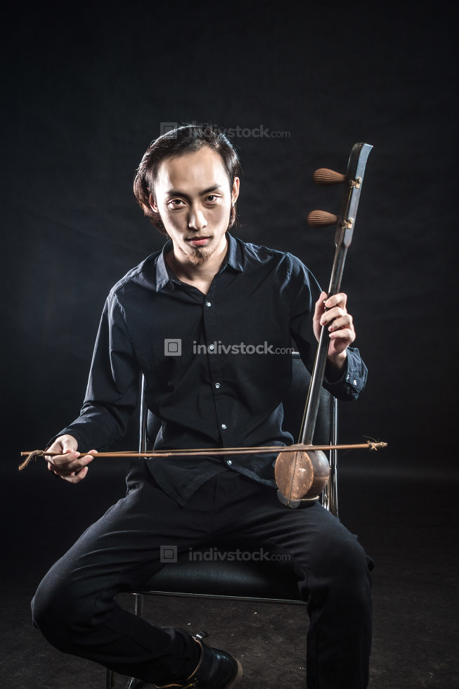 man is playing huqin