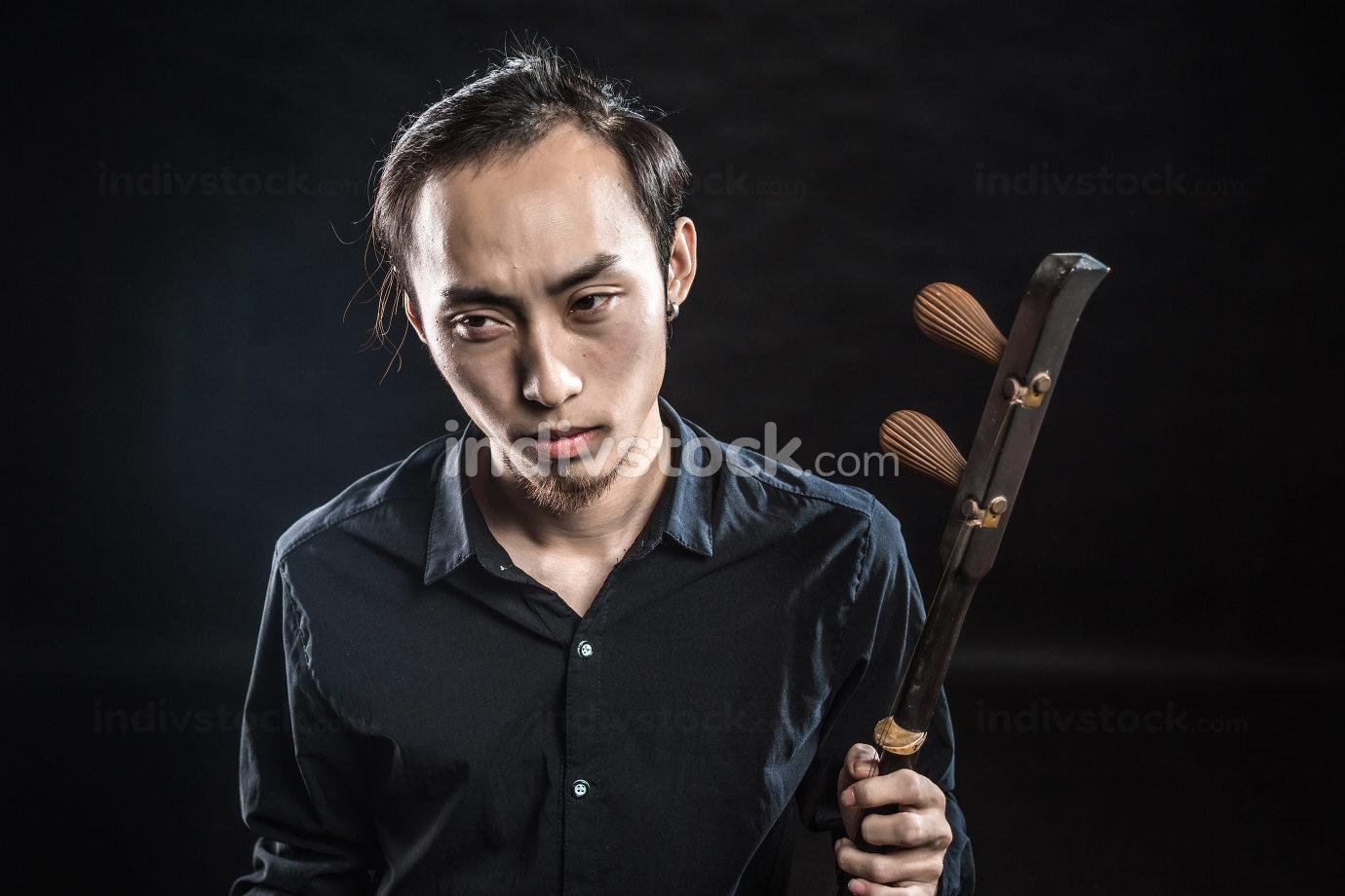 man is playing huqin