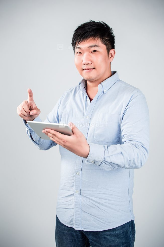 man using digital tablet against gray background