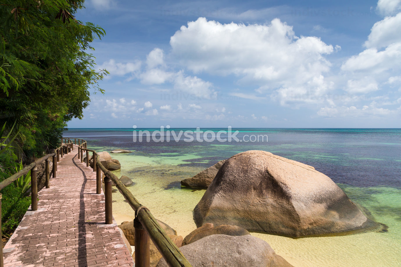 Pathway by the ocean with big stones and green plants
