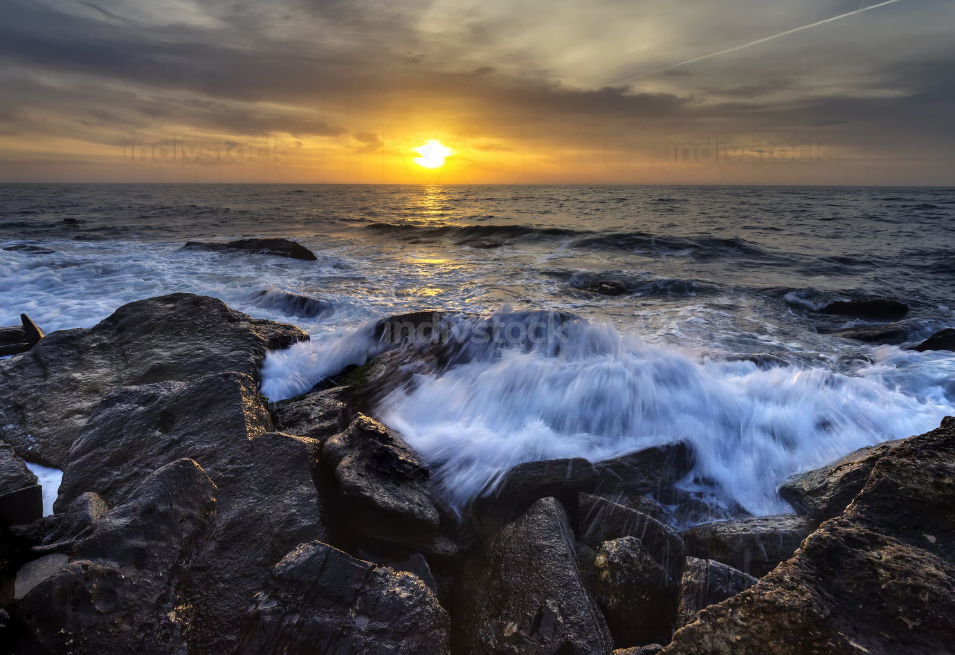 Stormy sea with the colorful sunrise sky at the rocky coastline of the Black Sea