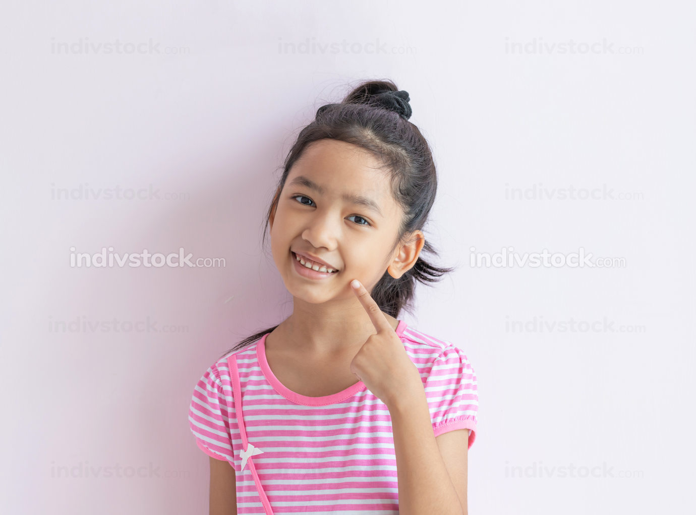 The child with black hair is smiling and pointing to her face.
