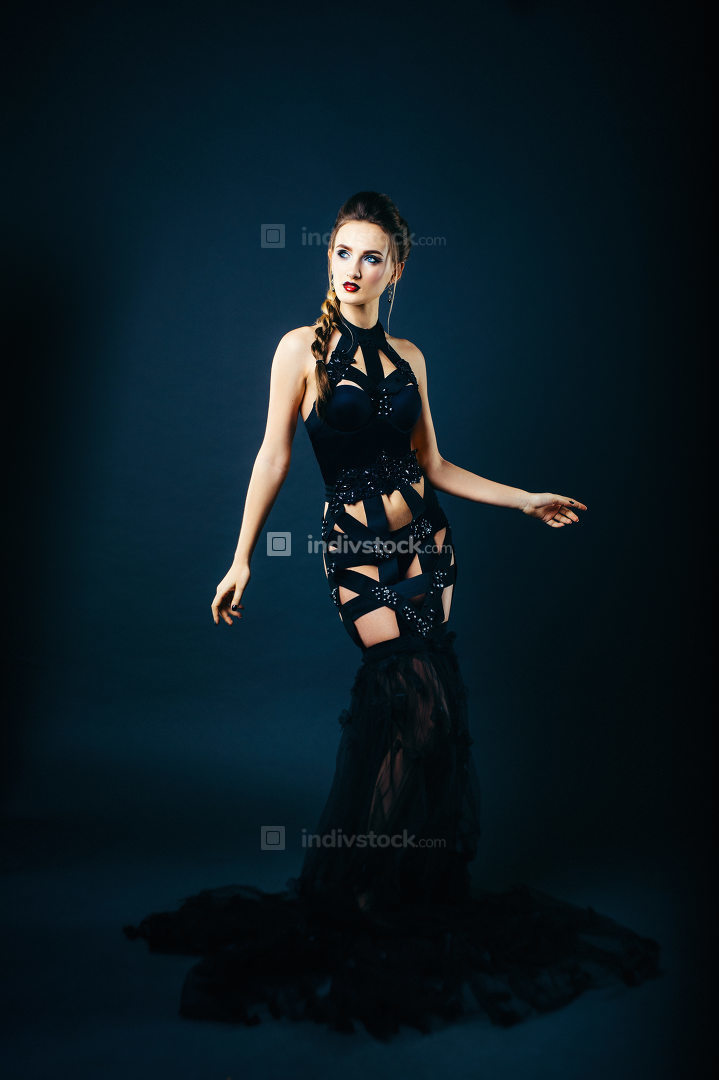 white girl modell on a dark background in a dress made of cut st