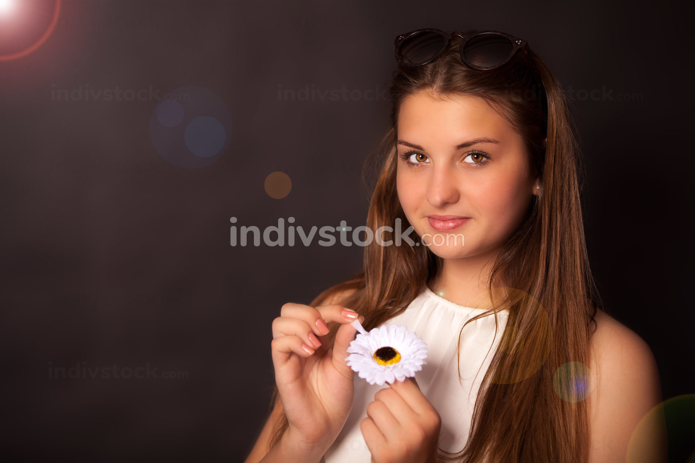 Young girl with a flower and sun glasses