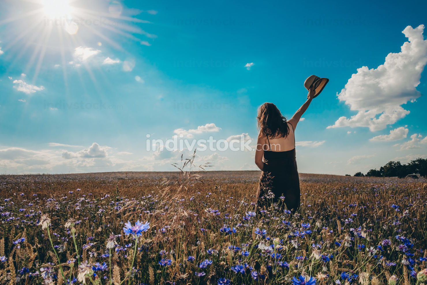 Young woman in straw hat watching the sun