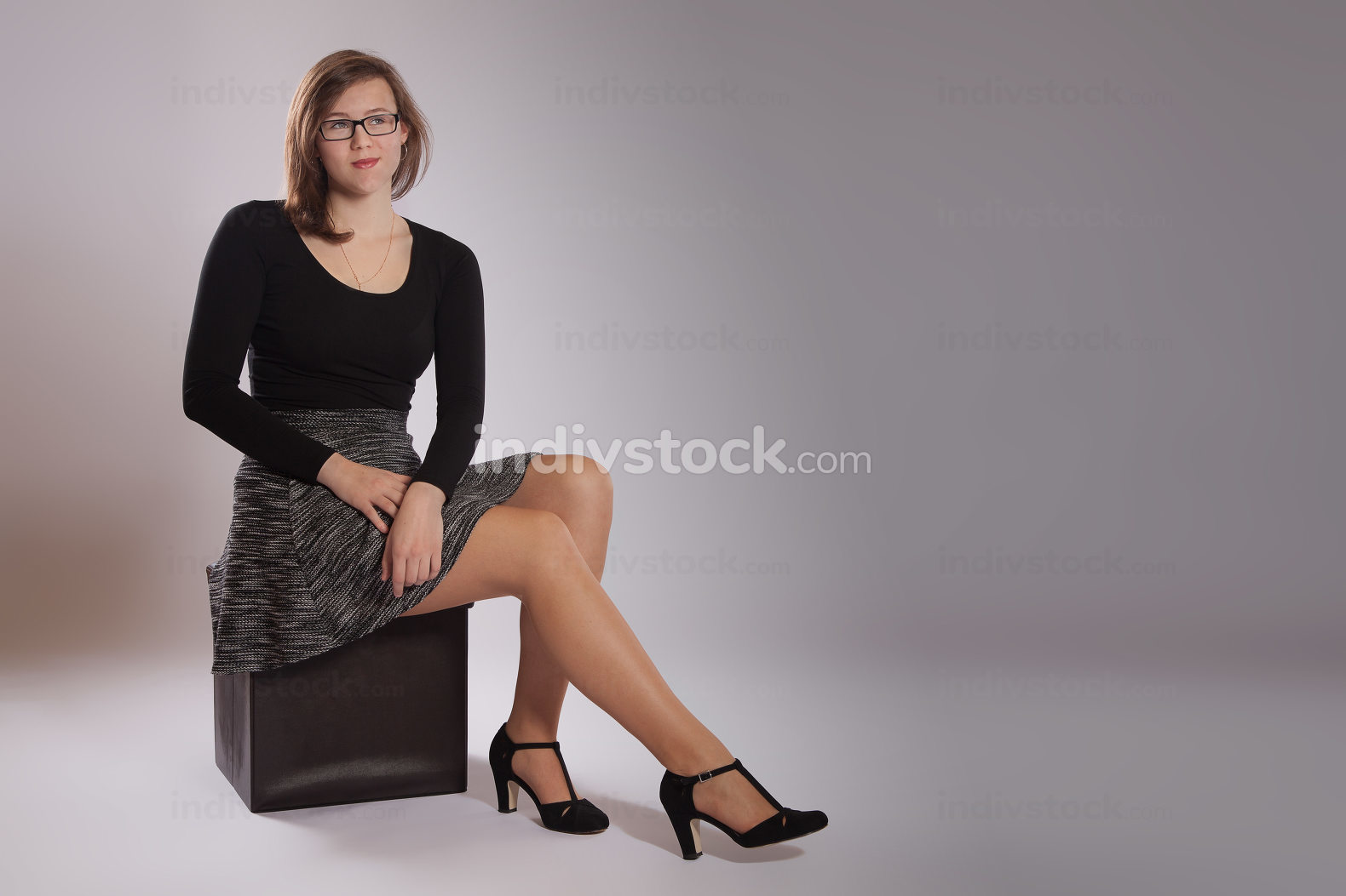 Young woman is sitting on a stool