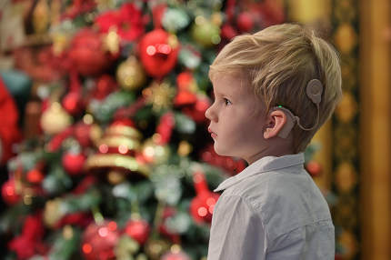 A Boy with Cochlear Implants and Christmas tree in background