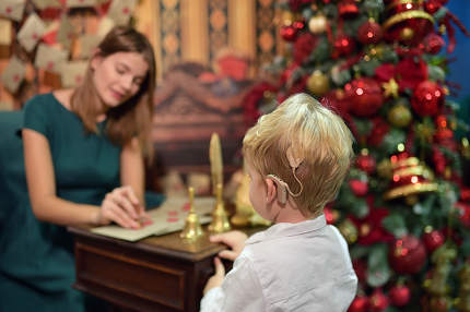 A Boy with Cochlear Implants Seal Letter To Santa Claus For New Year