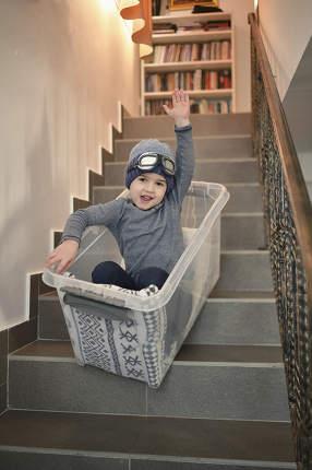 Boy having fun sledding down stairs in a storage box. Little Boy having fun sledding down stairs in a storage box