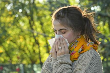 Girl in autumn park sneezing in tissue