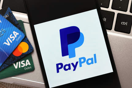 Krakow, Poland - October 16, 2020:  PayPal sign on the smartphone screen next to Visa and Mastercard cards