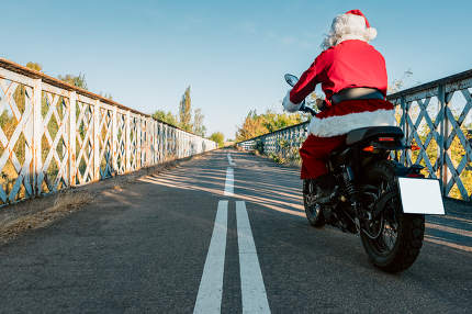 santa claus riding a motorcycle on the road