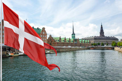 the flag of Denmark on the background of The Historic Old Town of Copenhagen