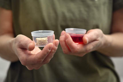 Woman Hands Takes Communion In One Time Use Containers To Protect From The Virus