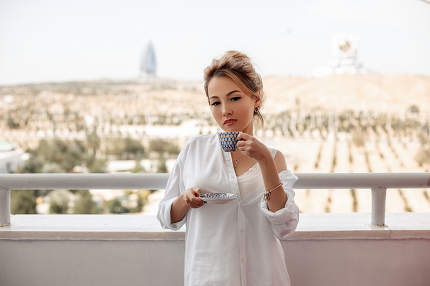 young beautiful Asian girl in beige lace shorts,white shirt drinking coffee standing on the balcony. selective focus. small focus area.